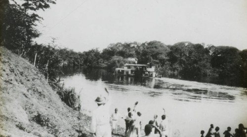 Black and white lantern slide showing a European missionary and a group of Congolese (dressed in European attire) waving off a two decked steamer at Baringa Beach at the side of the Congo River.  Courtesy University of Southern California Digital Collections.